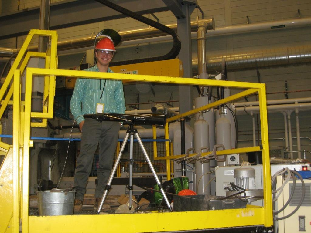 This is a picture of Samuel Arnold and his optical setup measuring the off gas spectral emissions from an air induction furnace melt at the CANMET steel research facility in Hamilton. This pilot scale test is being used to prove the functionality of my optical setup and determine areas of improvement for full scale testing and validation of laboratory results.